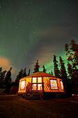 The Aurora Borealis (Northern Lights) over an illuminated yurt outside of Whitehorse in the Yukon Territory, Canada., Whitehorse, Yukon Territory, Canada