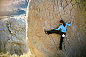 Woman bouldering on an overhang, Buttermilk Boulders, California, United States