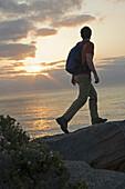 Hiker on cliff trail on rocky ocean coast Sydney, New South Wales, Australia