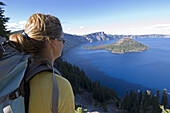 Hiker along cliff trail near lake Crater Lakes National Park, Oregon, United States