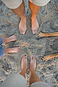 Group of feet and dog paws on sand Long Beach, California, United States
