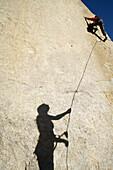 Female belay shadow on rock, Bishop, California, United States