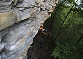 A female climber swings from a rock face, Jasper, Tennessee, United States