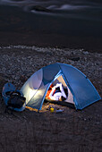 Woman camps in tent by a river Durango, Colorado, United States