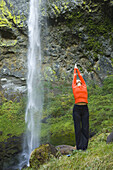Woman does yoga in front of waterfall, Columbia River Gorge, Oregon, United States