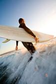 A male surfer runs into the water in California Hermosa Beach, California, USA