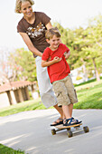 A smiling young boy rides a skateboard with his mom on a sunny summer afternoon in a grassy park in Huntington Beach, California, Huntington Beach, California, United States