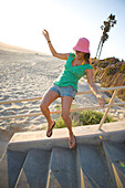 A woman slides down the railing of a starwell leading down to the beach on a summer evening Huntington Beach, California, United States