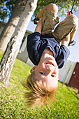 A smiling young boy hangs upside down from a swing in the backyard of his family's home on a sunny summer afternoon Costa Mesa, California, United States