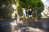 A mother jumps on a trampoline with her two children in the backyard of the family's home on a sunny summer afternoon Costa Mesa, California, United States