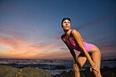 An elete female swimmer stretches on a rocky ocean shoreline after returning from a swim in Palos Verdes, California Palos Verdes, California, United States
