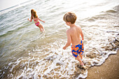 A young girl and boy enjoy a sunny summer afternoon at the beach in Huntington Beach, California Huntington Beach, California, United States