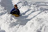 A young girl sledding, Newry, Maine Newry, Maine, USA