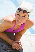An athletic woman rests on the side of a pool after a challenging workout Long Beach, California, United States