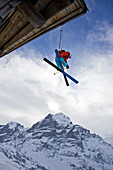 A young man skis off the roof of an alpine hut in Grindalwald, Switzerland Grindelwald, Jungfrau region, Switzerland