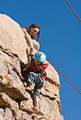 Mother helping child finish a rock climb, Joshua Tree National Park, California 29 Palms, California, USA