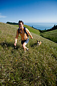 A woman hiking in grassy hills along the coast with her dog San Francisco, California, USA