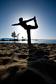 Silhouette of a woman doing yoga on a beach by a lake in the mountains South Lake Tahoe, California, USA