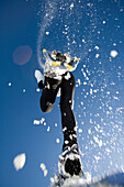 woman jumps overhead in snowshoes