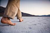 A man walks barefoot on the salt flats of Death Valley National Park, California Death Valley National Park, California, USA