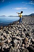 A young boy throws a stone into a large body of water in Loreto, Baja California Sur, Mexico Loreto, Baja, Mexico