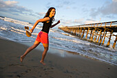 A smiling woman running on the beach at sunrise on a spring morning in Newport Beach, California Newport Beach, California, USA