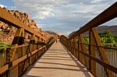 Two people in distance walking across bridge in Moab, Utah Moab, Utah, USA