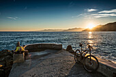 Mountain biker resting on quay wall in sunset, Varigotti, Finale Ligure, Province of Savona, Liguria, Italy
