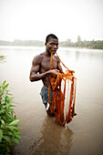 Young man fishing with cast net in river Mono, Agbanakin, near Grand-Popo, Mono Department, Benin