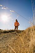 Full view of woman jogging on dirt road, San Rafael, CA