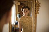 Woman wearing fancy dress looking in mirror, Seattle, WA