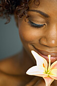 Close up of African woman smelling flower, Austin, TX