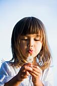Asian girl blowing a dandelion, Bellingham, WA