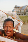 African woman laying in hammock at beach, Norfolk, VA