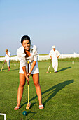 Young woman playing croquet, Cape Cod, MA