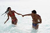 South American couple running in water, Morrocoy, Venezuela
