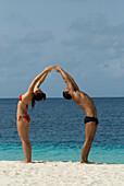 Multi-ethnic couple practicing yoga at beach, Morrocoy, Venezuela
