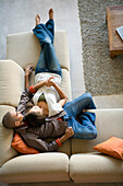 African American couple laying on sofa, Cape Town, South Africa