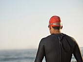 Rear view of Hispanic man wearing wetsuit, Newport Beach, CA