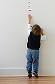 Boy reaching for height markers on wall, Richmond, VA