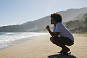 African man crouching at beach, Caruao, Venezuela