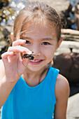 Asian girl holding tiny crab, Bellingham, WA