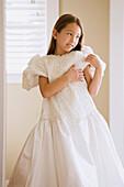 Asian girl trying on wedding dress, Seattle, WA