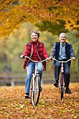 African couple riding bicycles in park in autumn, Seattle, WA