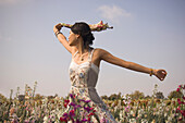 Asian woman with arms outstretched in meadow, California