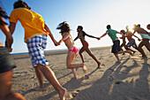 Multi-ethnic group of friends running on beach, Santa Monica, CA