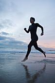 Hispanic woman in wetsuit running on beach, Newport Beach, CA