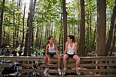 Women in sportswear sitting on bridge railing