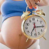 Pregnant Hispanic woman holding alarm clock, Jersey City, NJ