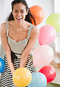 Laughing mixed race woman with balloons, Jersey City, New Jersey
